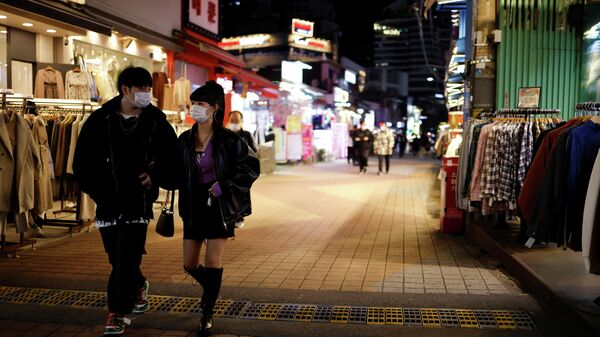 Прохожие на опустевшей торговой улице в Сеуле, Южная Корея