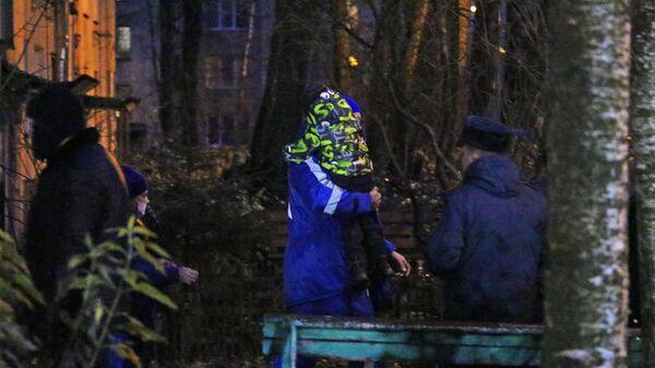 Сотрудник скорой помощи несет одного из шестерых детей, освобожденных после захвата в городе Колпино Ленинградской области
