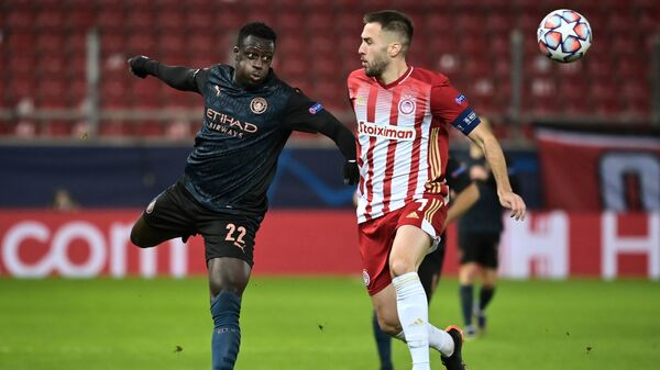 Manchester City's French defender Benjamin Mendy (L) fights for the ball with Olympiakos' Greek midfielder Kostas Fortounis during the UEFA Champions League group stage football match between Olympiakos and Manchester City, on November 25, 2020 at Georgios-Karaiskakis stadium in Piraeus, near Athens. (Photo by ARIS MESSINIS / AFP)