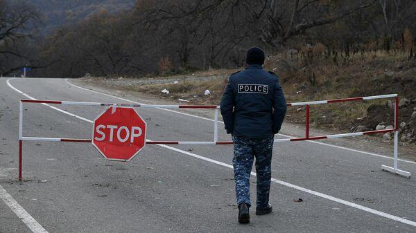 Полицейский возле контрольно-пропускного пункта на автомобильной дороге Варденис-Мартуни у населенного пункта Гетаван, Азербайджан