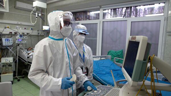 Врачи у аппарата УЗИ в отделении реанимации и интенсивной терапии в госпитале COVID-19 в городской клинической больнице № 52 в Москве