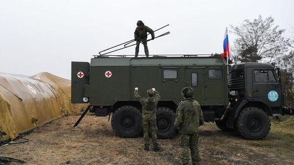 Российские военнослужащие выгружают оборудование на территории мобильного полевого госпиталя неподалеку от Степанакерта