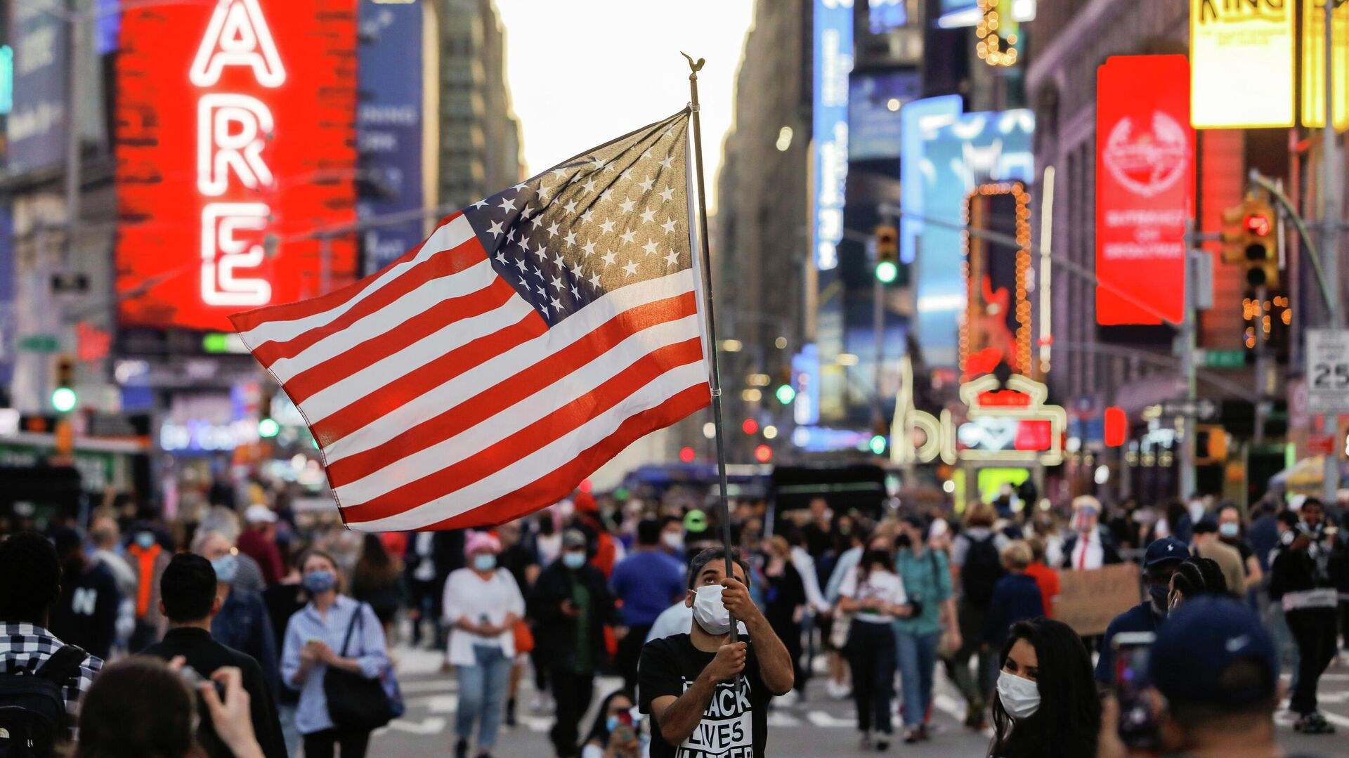 Мужчина с флагом США на Таймс-сквер в Нью-Йорке - РИА Новости, 1920, 01.12.2020