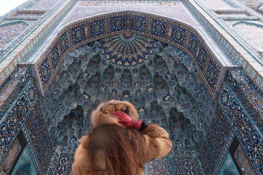 Девушка рассматривает сотовый свод портала Санкт-Петербургской соборной мечети