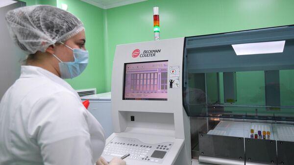 Лаборант Научного Центра по профилактике и борьбе со СПИДом в Москве проводит исследование крови на ВИЧ-инфекцию