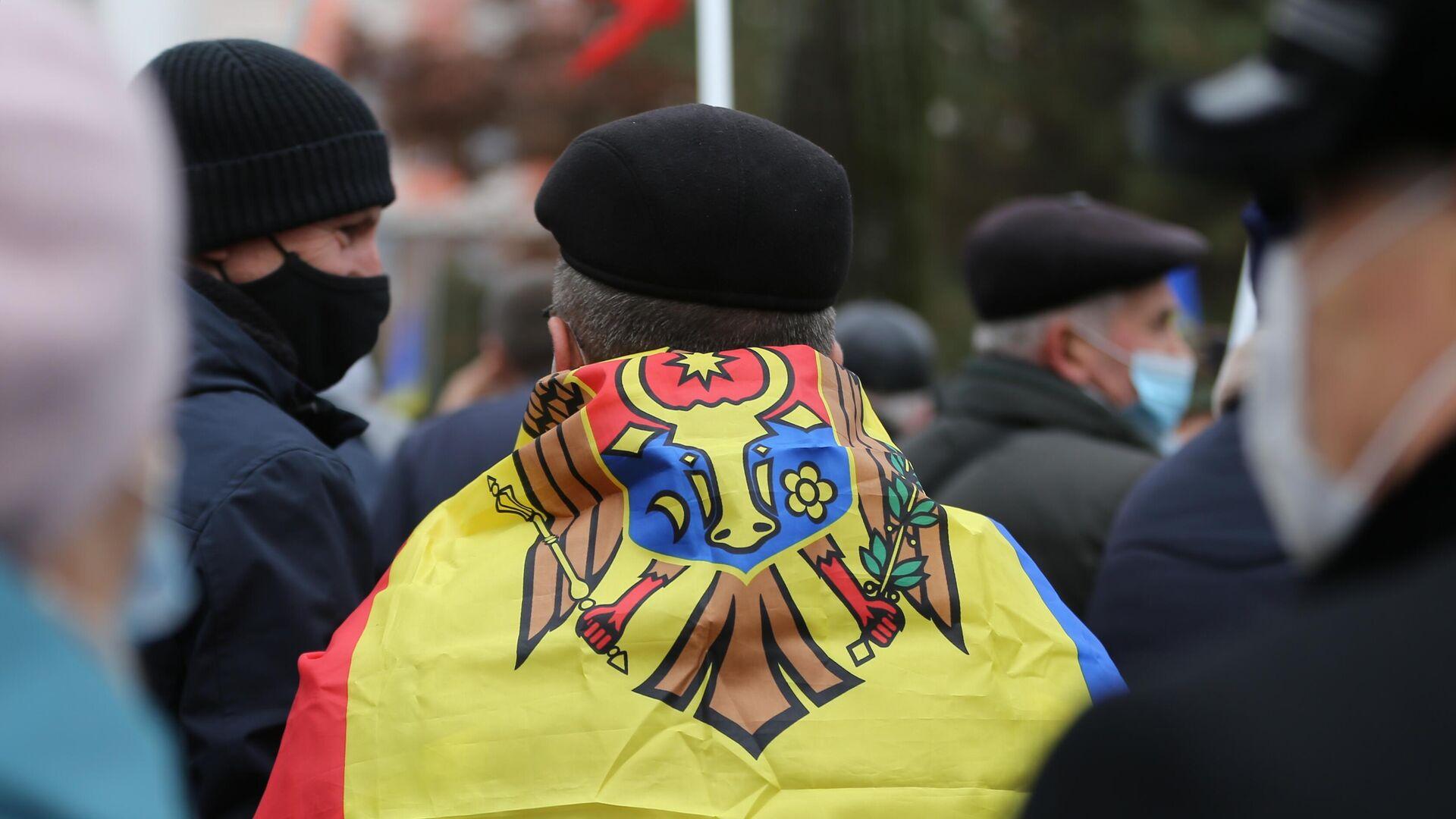 Флаг Молдавии на спине участника акции сторонников избранного президента Молдавии Майи Санду у здания парламента в Кишиневе - РИА Новости, 1920, 07.12.2020