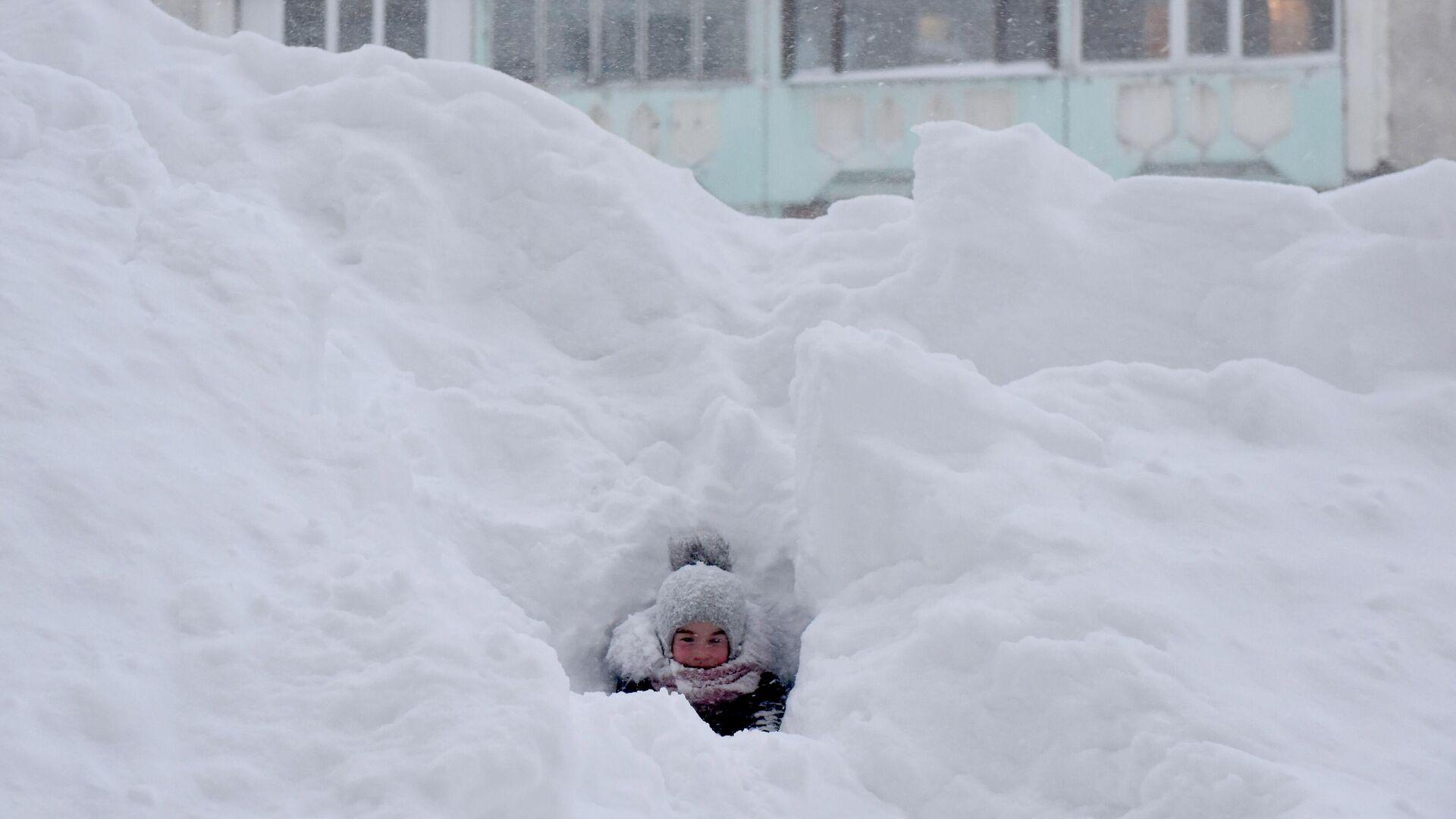 Ребенок играет в сугробе во дворе жилого дома в Норильске - РИА Новости, 1920, 28.12.2020