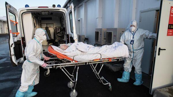 Медицинские работники во время транспортировки пациентки в госпитале для больных COVID-19 в МКЦИБ Вороновское