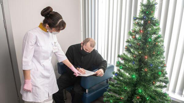 Медработник и пациент в прививочном пункте по вакцинации от COVID-19