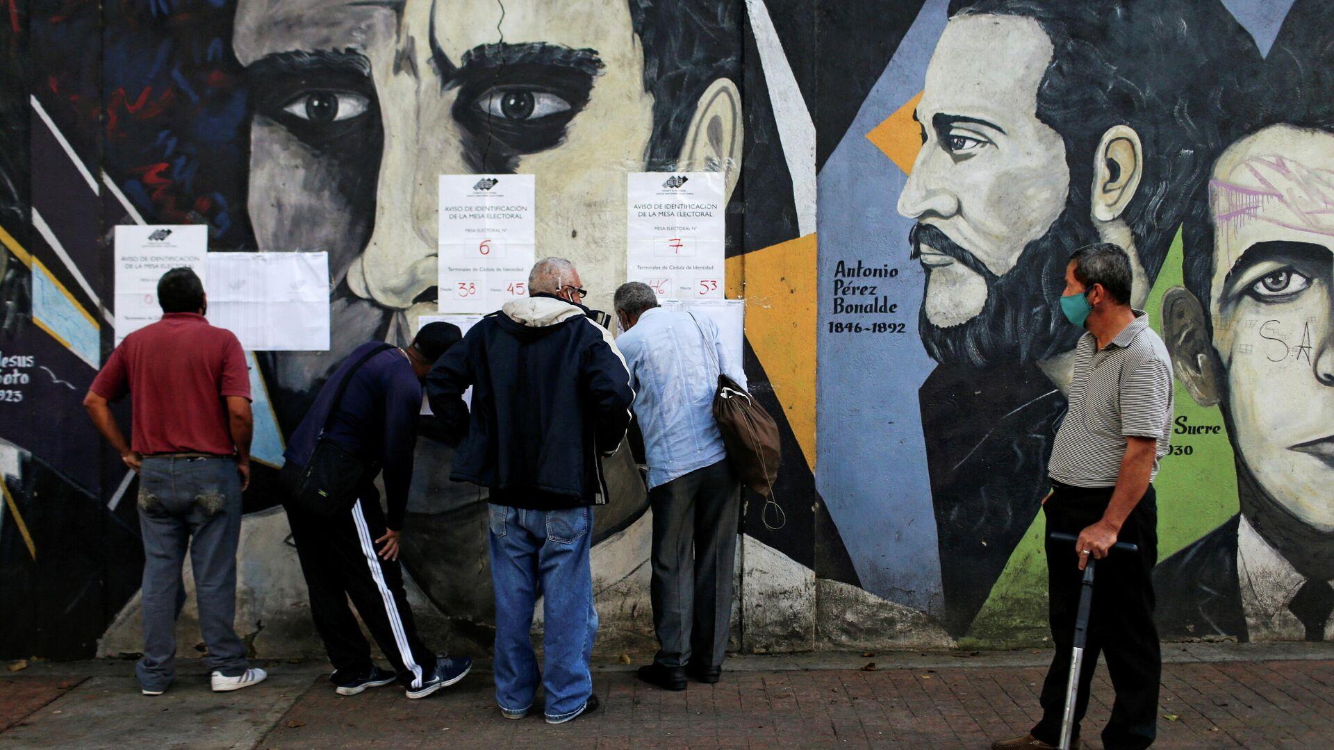 Люди проверяют списки возле избирательного участка во время парламентских выборов в Каракасе, Венесуэла - РИА Новости, 1920, 07.12.2020
