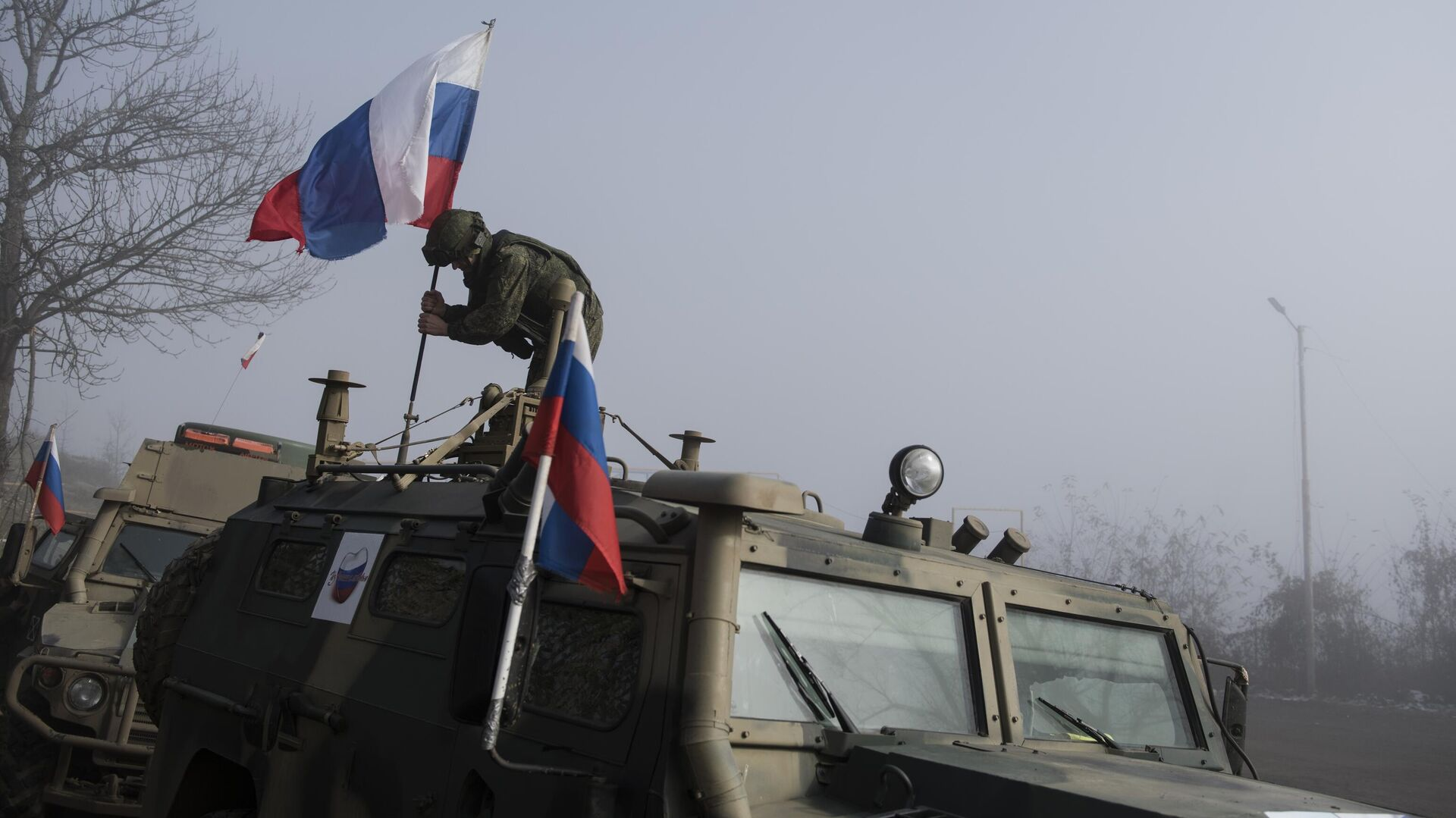 Российский миротворец устанавливает флаг на бронеавтомобиле на блокпосту №6 на въезде в город Шуша на дороге из Степанакерта в Лачин - РИА Новости, 1920, 29.07.2021