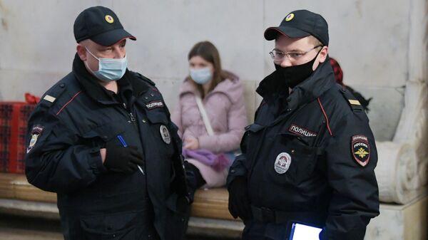 Представители правоохранительных органов в защитных масках на станции в московском метрополитене