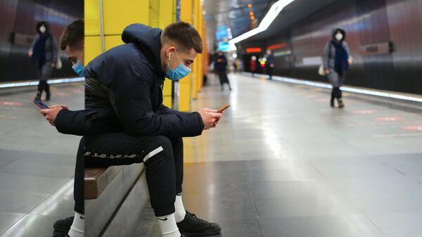 Молодой человек в защитной маске на платформе метро Жулебино Московского метрополитена