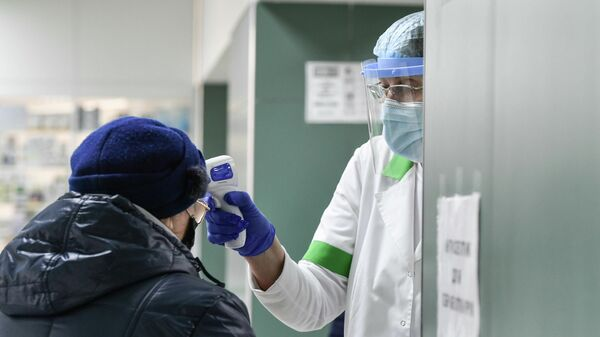 Медицинский работник проверяет температуру у пожилой женщины
