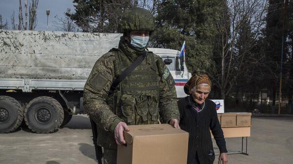 Военнослужащий российского центра по примирению враждующих сторон раздает гуманитарную помощь жителям города Мартакерт