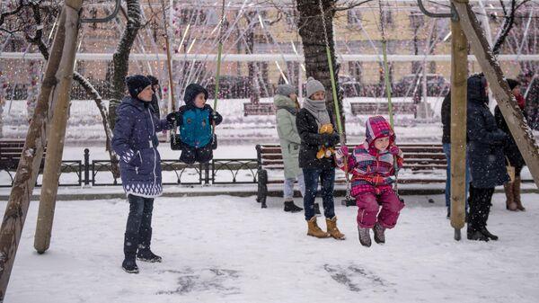 Дети с родителями качаются на качелях на Тверском бульваре в Москве