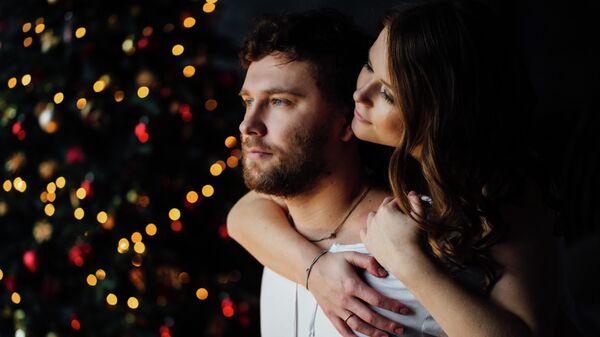 Молодая пара возле новогодней елки