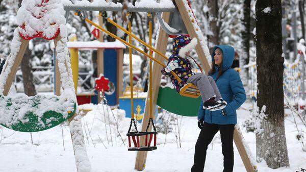 Женщина с ребенком на детской площадке Фестивального сквера в Краснодаре после снегопада