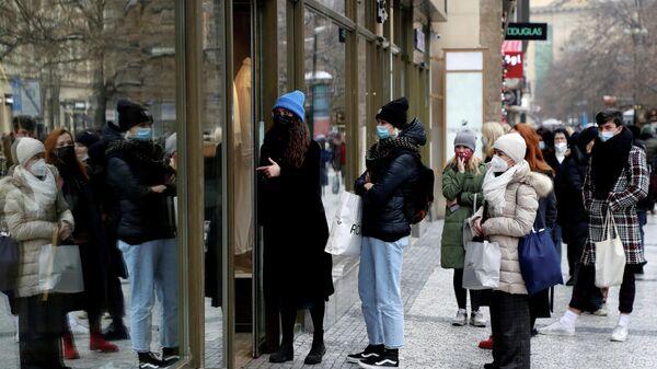 Покупатели в очереди перед магазином в Праге
