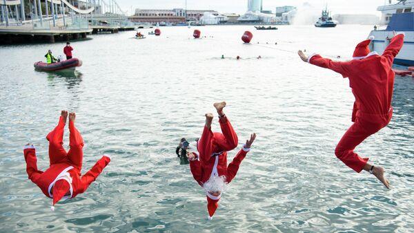 Мужчина в костюмах Санта-Клауса прыгают в воду во время 111-го соревнования по плаванию Copa Nadal в порту Велл в Барселоне. 25 декабря 2020