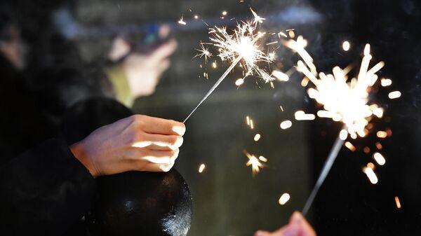 Бенгальские огни в руках людей, празднующих Новый год