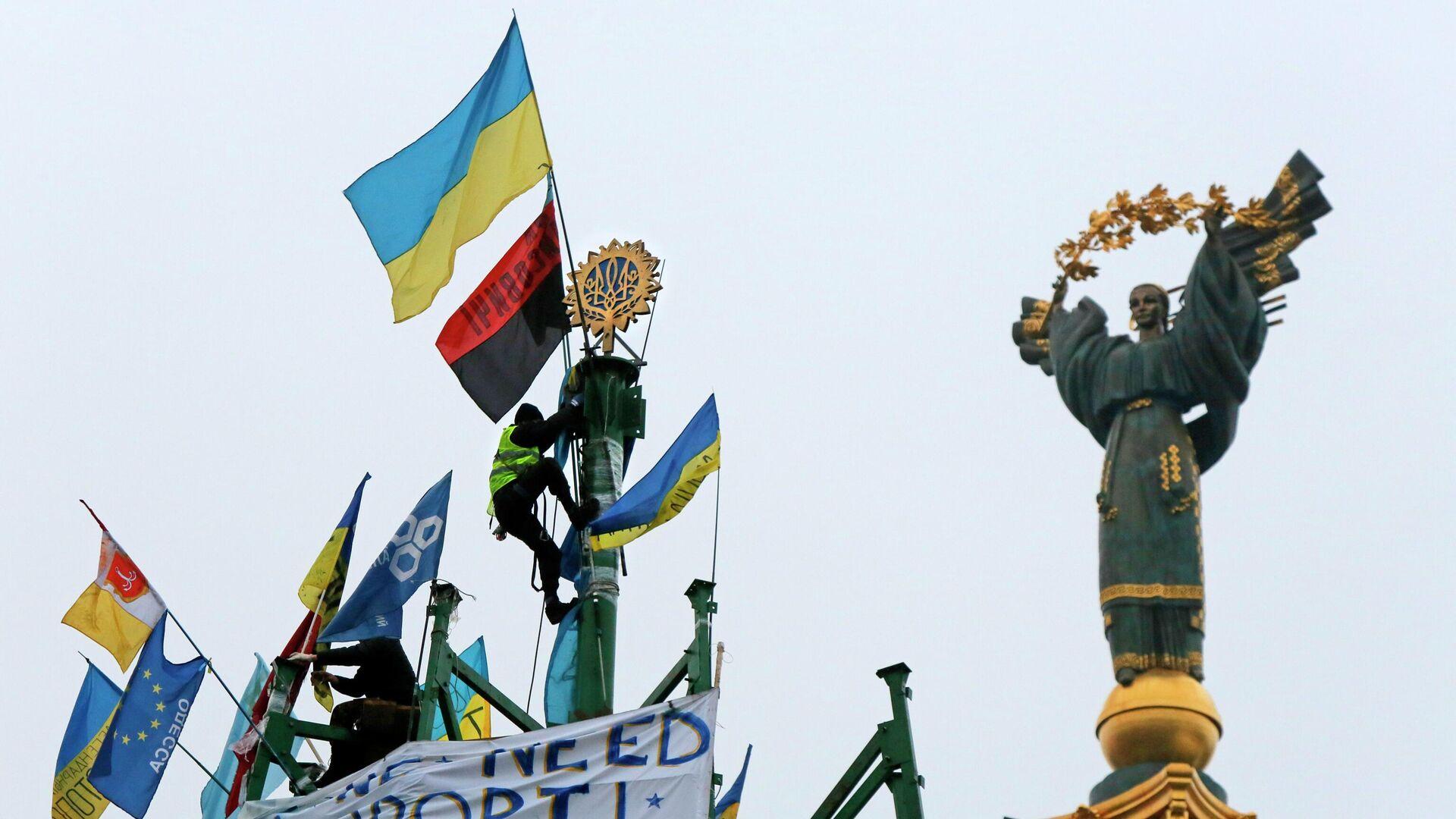 Активист проевропейского союза укрепляет украинский герб и флаг на металлической основе разрушенной елки во время митинга на площади Независимости в Киеве - РИА Новости, 1920, 15.09.2021