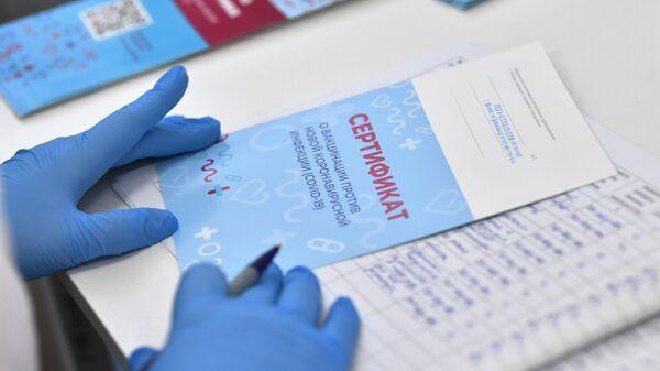 Медицинская сестра выписывает пациенту сертификат о вакцинации против коронавирусной инфекции