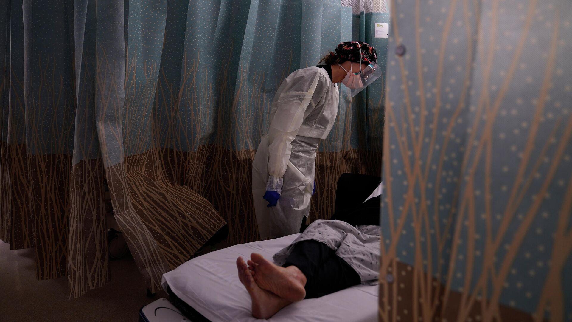 Медсестра разговаривает с пациентом, у которого проявляются симптомы коронавируса, в отделении неотложной помощи Медицинского центра в Лос-Анджелесе - РИА Новости, 1920, 05.01.2021