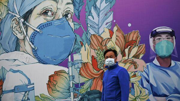 Мужчина в маске проходит мимо граффити, посвященному врачам, в Китае