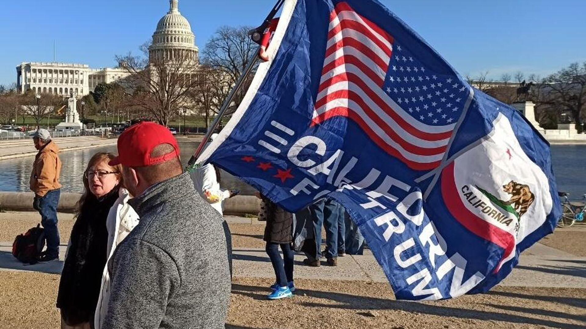 Мужчина с флагом сторонников Дональда Трампа на Капитолийском холме в Вашингтоне - РИА Новости, 1920, 10.01.2021