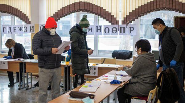 Избиратели на одном из избирательных участков в Бишкеке во время голосования на досрочных выборах президента Кыргызской Республики и референдуме по вопросу формы правления