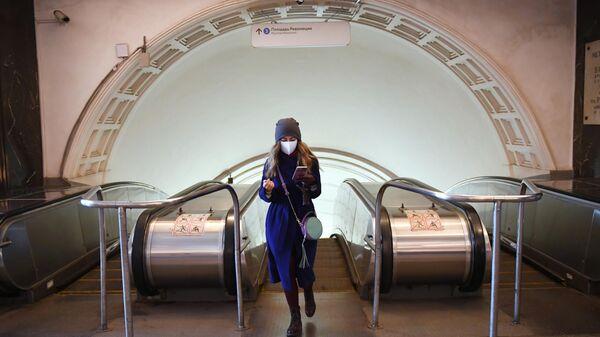 Девушка поднялась по эскалатору станции метро Площадь революции