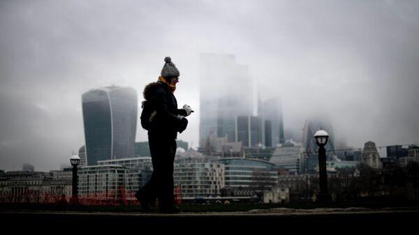 Женщина проходит мимо Сити Лондон