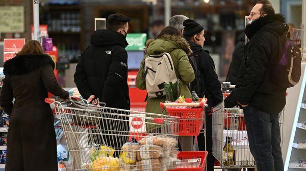 Покупатели в очереди возле кассы в гипермаркете Ашан