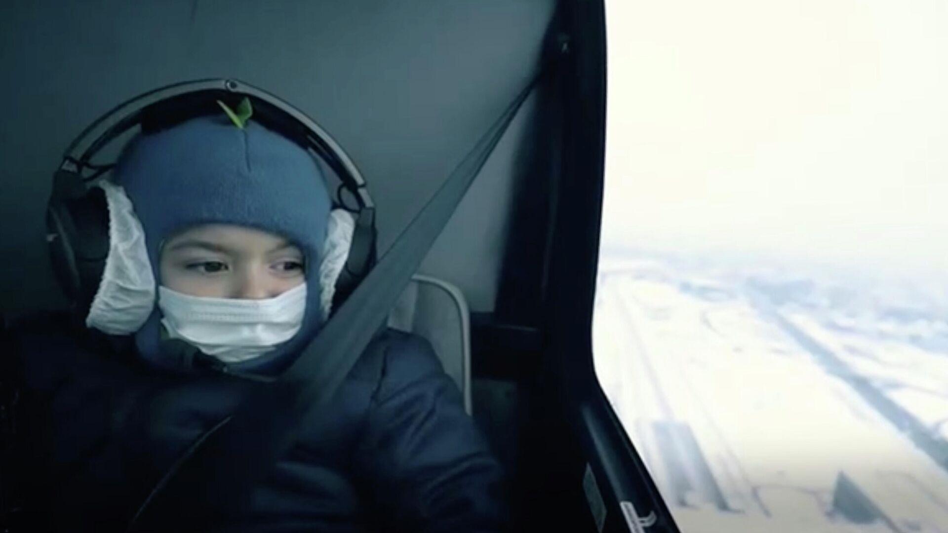 Пятилетний Марк во время полета на вертолете. Стоп-кадр видео - РИА Новости, 1920, 15.01.2021