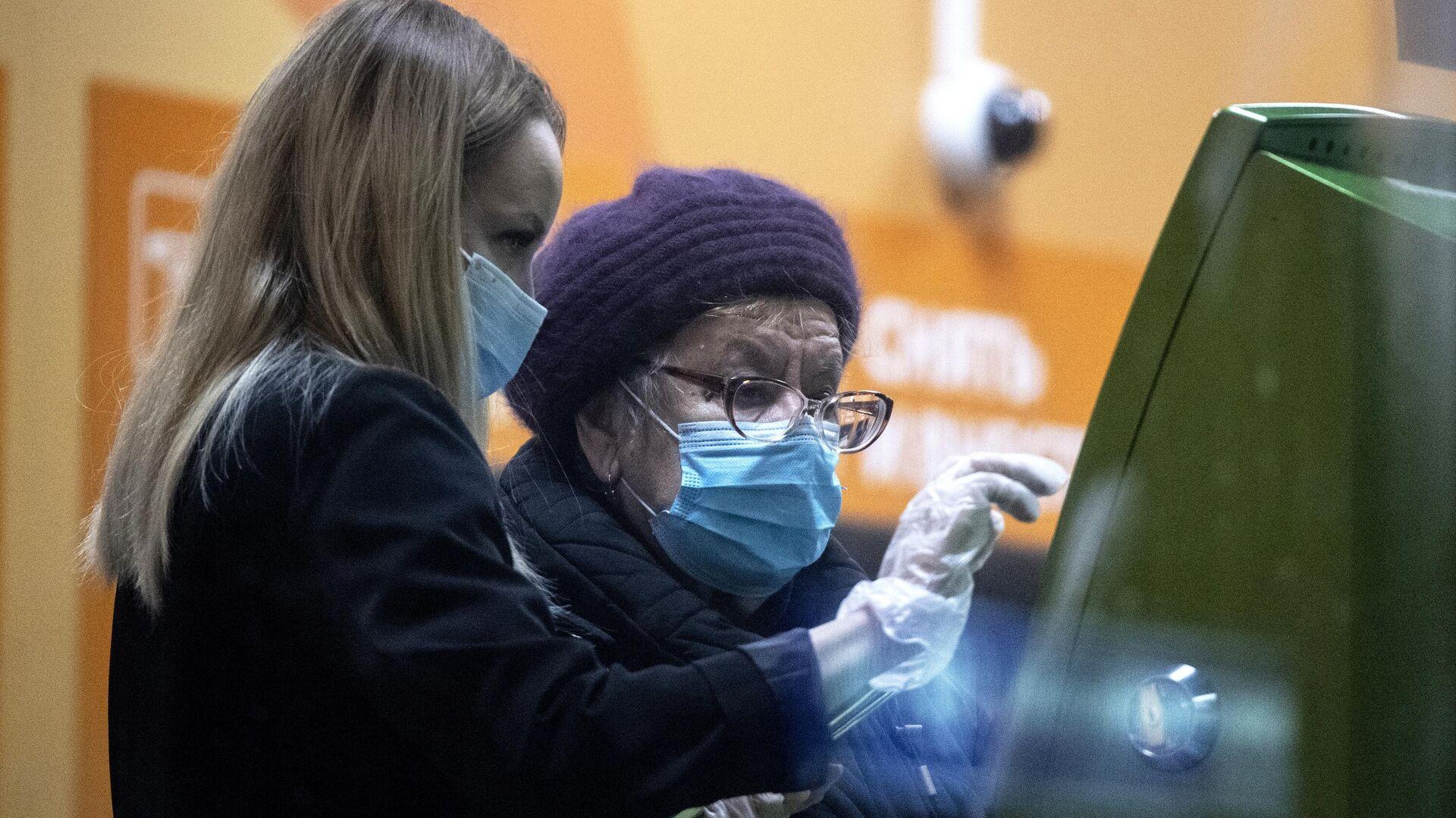 Сотрудница в отделении Сбера помогает женщине у банкомата - РИА Новости, 1920, 23.01.2021