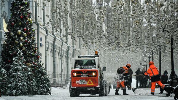 Сотрудники муниципальных служб чистят снег на одной из улиц в Москве