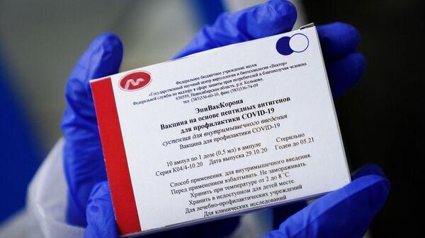 Медработник демонстрирует вакцину ЭпиВакКорона