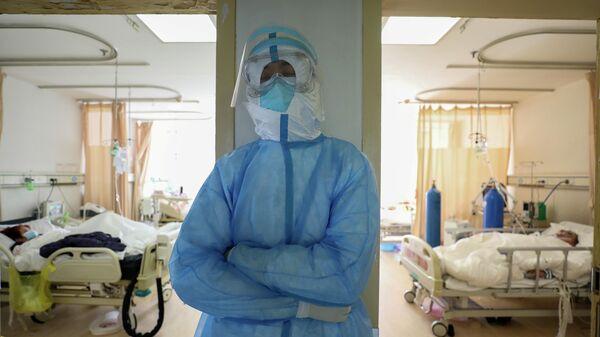 Медицинский работник в защитном костюме в больнице Уханя, Китай