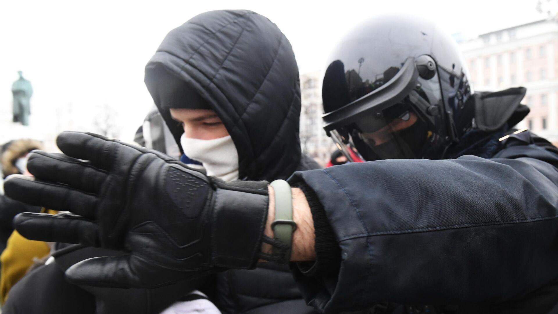 Сотрудник правоохранительных органов задерживает участника несанкционированной акции сторонников Алексея Навального в Москве - РИА Новости, 1920, 23.01.2021