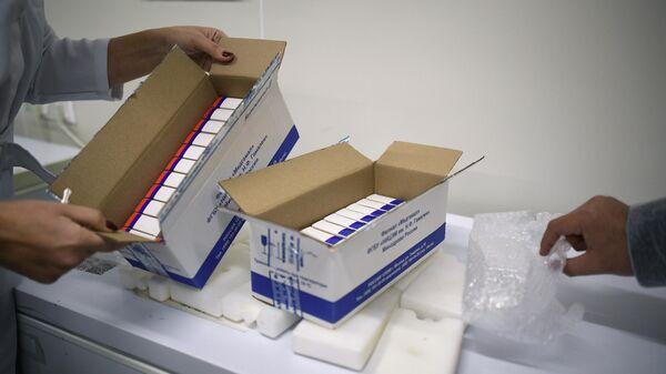 Сотрудница упаковывает вакцину Гам-КОВИД-Вак (торговая марка Спутник V) для отправки за границу