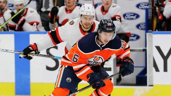 Хоккеисты Артем Зуб (на заднем плане) и Кайлер Ямамото во время матча НХЛ