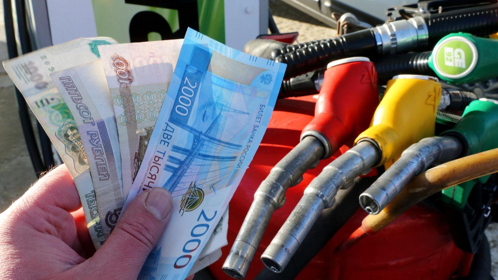 Деньги на оплату топлива в руке мужчины на АЗС сети ННК в Хабаровске - РИА Новости, 1920, 14.07.2021
