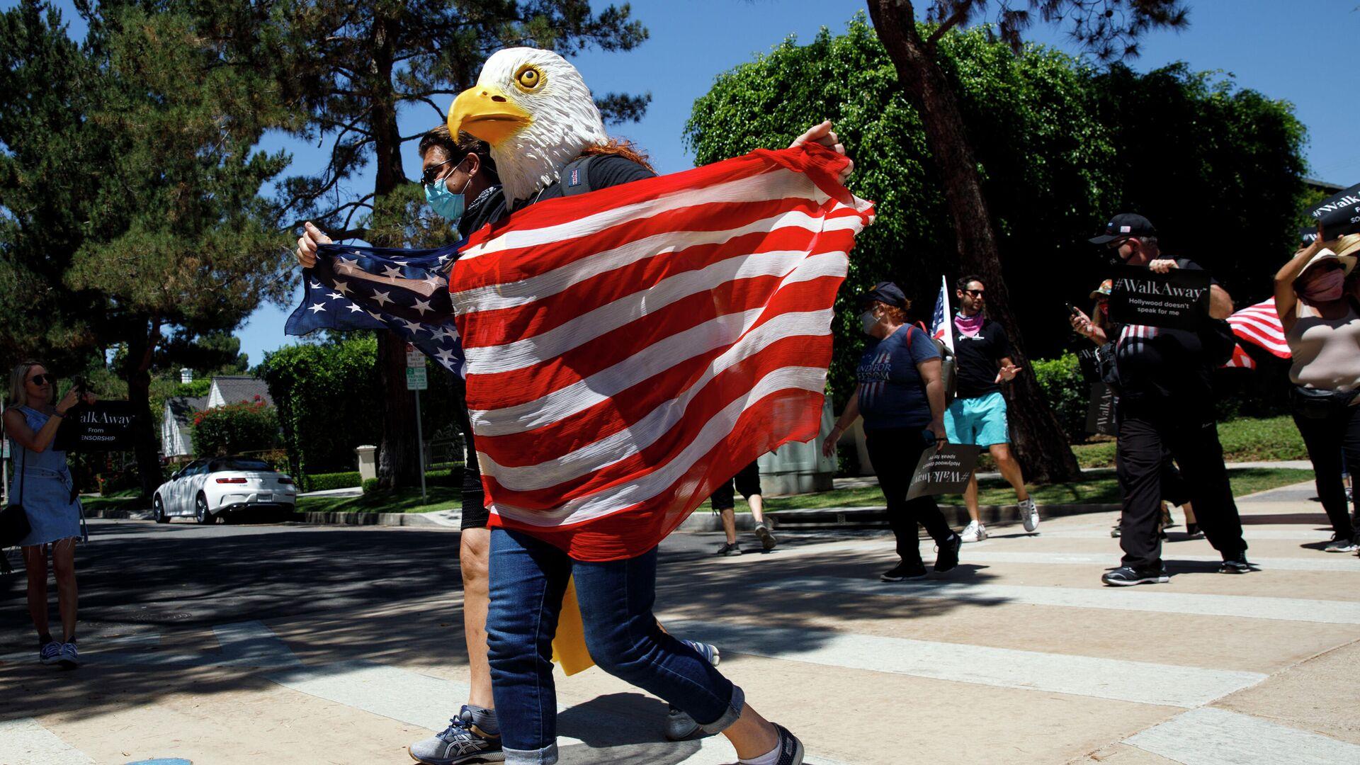 Демонстрант в маске орла с флагом США в Калифорнии - РИА Новости, 1920, 01.05.2021