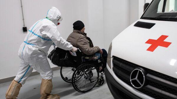 Медик везет пациента в приемное отделение городской клинической больницы №40 в Москве
