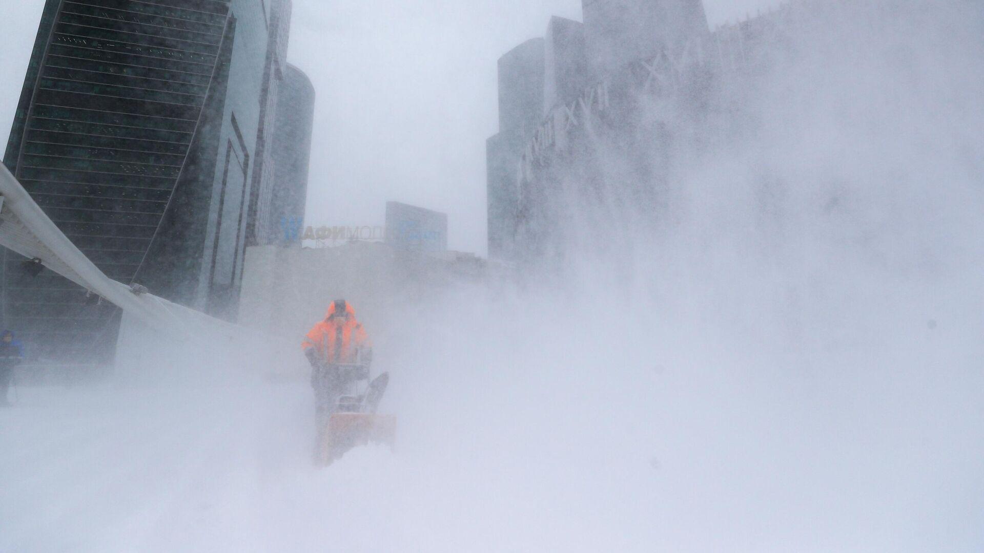 Сотрудник коммунальной службы убирает снег с площади у делового центра Москва-сити - РИА Новости, 1920, 13.02.2021