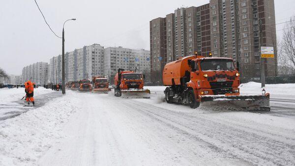 Сотрудники коммунальной службы убирают снег на улице в Москве во время снегопада