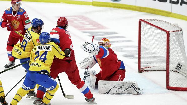 Russia's goalkeeper Alexander Samonov (R) makes a save during the Beijer Hockey Games (Euro Hockey Tour) ice hockey match between Sweden and Russia in Malmo on February 13, 2021. (Photo by Anders Bjuro / TT NEWS AGENCY / AFP) / Sweden OUT