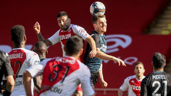 Monaco's Chilean defender Guillermo Maripan (Top-L) fights for the ball with Lorient's French defender Julien Laporte (Top-R) during the French L1 football match between AS Monaco and FC Lorient at The Louis II Stadium in Monaco on February 14, 2021. (Photo by Valery HACHE / AFP)
