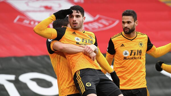 Wolverhampton Wanderers' Portuguese midfielder Pedro Neto (C) celebrates with teammates after scoring their second goal during the English Premier League football match between Southampton and Wolverhampton Wanderers at St Mary's Stadium in Southampton, southern England on February 14, 2021. (Photo by Andy Rain / POOL / AFP) / RESTRICTED TO EDITORIAL USE. No use with unauthorized audio, video, data, fixture lists, club/league logos or 'live' services. Online in-match use limited to 120 images. An additional 40 images may be used in extra time. No video emulation. Social media in-match use limited to 120 images. An additional 40 images may be used in extra time. No use in betting publications, games or single club/league/player publications. /